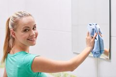 Happy woman cleaning mirror with rag Royalty Free Stock Photo