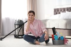 Happy woman with cleaning products sitting on floor royalty free stock image