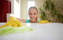 Happy woman cleaning table at home kitchen. People, housework and housekeeping concept - happy woman cleaning table at home kitchen Stock Image