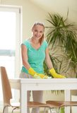 Happy woman cleaning table at home kitchen Stock Photography