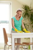 Happy woman cleaning table at home kitchen Stock Photos