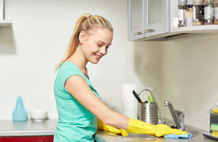 Happy woman cleaning table at home kitchen. People, housework and housekeeping concept - happy woman in protective gloves cleaning table with rag at home kitchen Royalty Free Stock Photography
