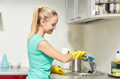 Happy woman cleaning tap at home kitchen. People, housework and housekeeping concept - happy woman in protective gloves cleaning tap with rag at home kitchen Stock Photos