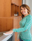 Happy woman cleaning TV Stock Images