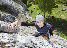 Happy woman climbing rock. Stock Photos