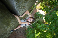 Happy woman climbing on a rocky wall rope, bouldering. Athletic female climber climbing on a rocky wall rope, bouldering. Smiling and looking towards the camera Stock Photo