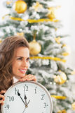 Happy woman with clock in front of christmas tree Stock Photography