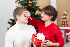 Happy woman closing man eyes by her hands with gift Stock Photo
