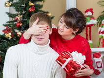 Happy woman closing man eyes by her hands with gift Stock Images