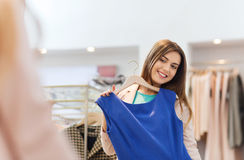 Happy woman with clothes at clothing store mirror Stock Photo