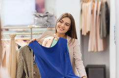 Happy woman with clothes at clothing store mirror Stock Image