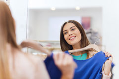 Happy woman with clothes at clothing store mirror Royalty Free Stock Photos