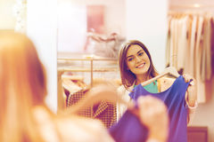 Happy woman with clothes at clothing store mirror. Shopping, fashion, style and people concept - happy woman choosing clothes and looking to mirror in mall or Royalty Free Stock Images