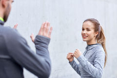 Happy woman with coach working out strike outdoors Royalty Free Stock Photography