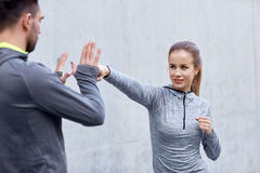 Happy woman with coach working out strike outdoors Stock Photography