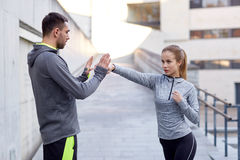 Happy woman with coach working out strike outdoors. Fitness, sport, martial arts, self-defense and people concept - happy women with personal trainer working out Royalty Free Stock Images