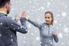 Happy woman with coach working out strike outdoors Royalty Free Stock Image