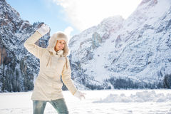 Happy woman in coat and fur hat throwing snow ball outdoors Stock Image
