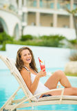 Happy woman with cocktail laying on chaise-longue Royalty Free Stock Image