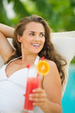 Happy woman with cocktail laying on chaise-longue Stock Photos