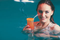 Happy woman with cocktail in water. Happy woman cocktail drink alcohol in swimming pool water. Pretty attractive girl relaxing Stock Photo