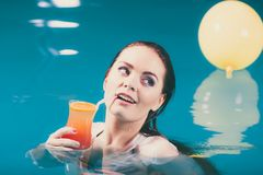 Happy woman with cocktail in water. Happy woman cocktail drink alcohol in swimming pool water. Pretty attractive girl relaxing Stock Images