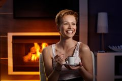 Happy woman with coffee in cosy room. Happy woman laughing, drinking coffee in cosy room by fireplace stock photos