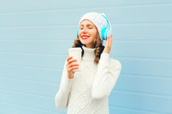 Happy woman with coffee cup enjoys listens to music in headphones wearing a knitted hat, sweater over blue Royalty Free Stock Photography