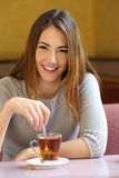 Happy woman in a coffee shop with a cup of tea Royalty Free Stock Photos