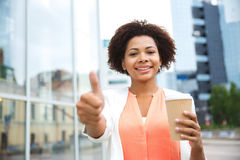 Happy woman with coffee showing thumbs up in city Stock Photos