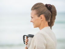 Happy woman on cold beach with cup of beverage Royalty Free Stock Photo