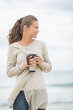 Happy woman on cold beach with cup of hot beverage Royalty Free Stock Image