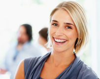 Happy woman with colleagues in background Stock Image