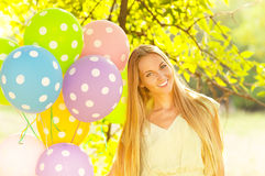 Happy woman with colored polka dots balloons. Portrait of a happy woman with colored polka dots balloons Royalty Free Stock Images