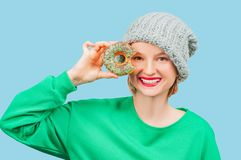 Happy woman with colorful donut against her eyes on pastel blue background royalty free stock photo