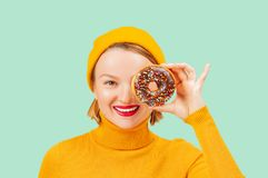 Happy woman with colorful donut against her eyes on pastel green background stock images