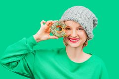 Happy woman with colorful donut against her eyes on pastel green background royalty free stock image