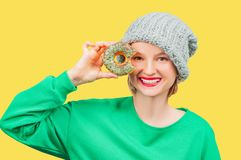 Happy woman with colorful donut against her eyes on pastel yellow background stock photos