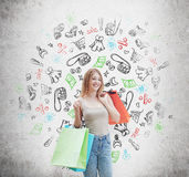 A happy woman with the colourful shopping bags from the fancy shops. Shopping icons are drawn on the concrete wall. Stock Photo