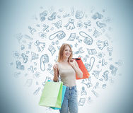 A happy woman with the colourful shopping bags from the fancy shops. Shopping icons are drawn on the wall. Royalty Free Stock Image