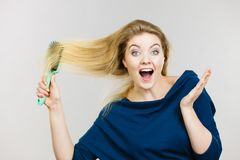 Woman brushing her long hair with brush. Happy woman combing her hair with brush. Young smiling female with natural blond straight long hairs, studio shot on Royalty Free Stock Photos