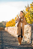 Happy woman in comfortable clothing is walking in autumn park Royalty Free Stock Image