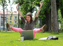 Happy Woman with Computer in an Urban Park. Excited happy woman with a laptop raising her hands and legs up in an urban park Royalty Free Stock Image