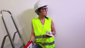 Happy woman construction worker near wall shows thumb up stock video footage