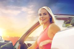Happy woman in convertible car over evening sky Royalty Free Stock Images
