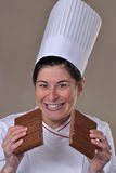 Happy woman cook dividing and holding chocolate Stock Image