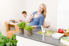 Happy woman cook enjoy white wine in kitchen Stock Photo
