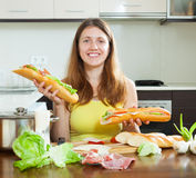 Happy woman with cooked sandwiches Stock Image