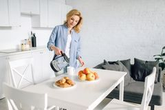 Happy woman cooking breakfast on the kitchen stock photography