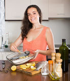 Happy woman cooking fish  in frying pan Royalty Free Stock Image